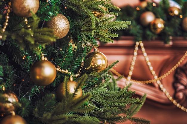 Rami di abete di un albero di natale decorato con palline d'oro giocattoli closeup