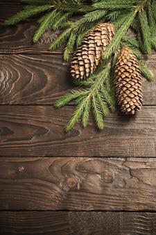 Rami di abete e cono su fondo di legno vecchio scuro