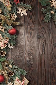 Rami di abete con decorazioni di natale sul vecchio fondo di legno scuro