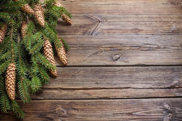 Rami di abete con coni su fondo di legno marrone