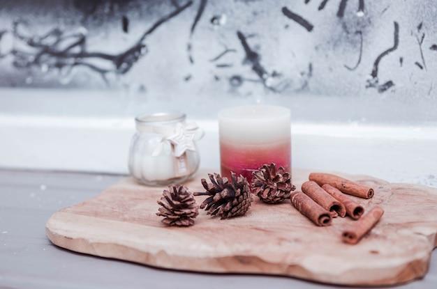 Pigne, bastoncini di cannella e candele sul pavimento