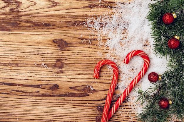 Rami di abete, neve e bastoncini di zucchero sulla tavola di legno