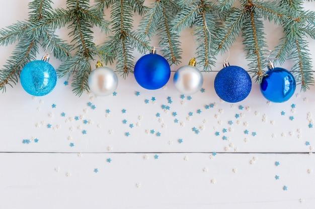 Rami di abete con decorazioni natalizie su bianco con copia spazio.