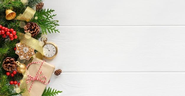 Rami di albero di abete con decorazioni natalizie orologio stile retrò e regalo su fondo di legno bianco.