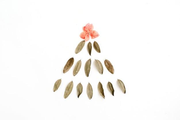 Abete fatto di foglie secche e bocciolo di fiore rosso