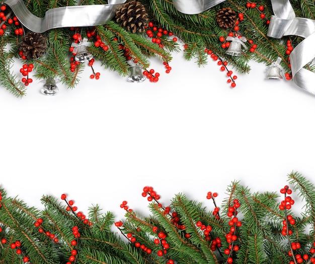 Ramoscelli di abete con decorazioni natalizie su bianco