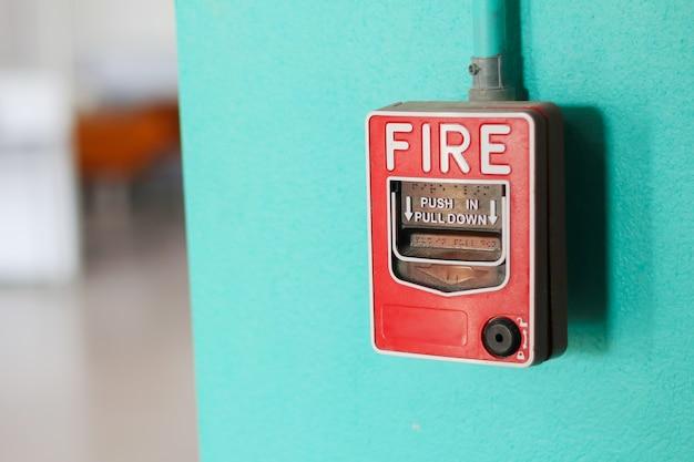 Interruttore di allarme antincendio sul muro verde in fabbrica.