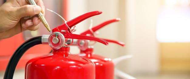 Ingegneria antincendio che controlla il livello del manometro dell'estintore.