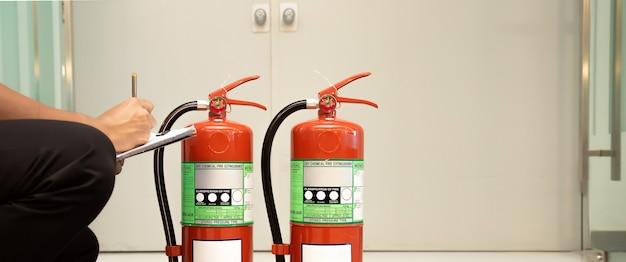 Ingegneria antincendio che controlla il livello del manometro del serbatoio degli estintori nell'edificio.