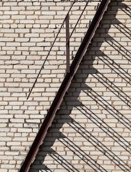 Via di fuga in caso di incendi su uno sfondo di muro di mattoni di un edificio, tempo soleggiato