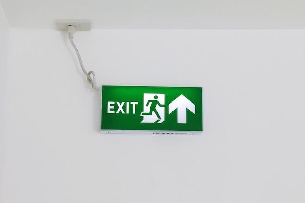 Segni dell'uscita di sicurezza, verde dell'uscita di sicurezza, segno della freccia sul muro bianco, segni d'emergenza, scatola leggera