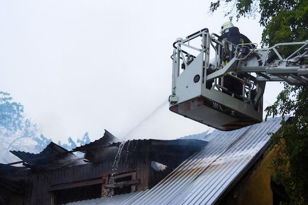 Combattente di fuoco che spegne le fiamme sul tetto in fiamme