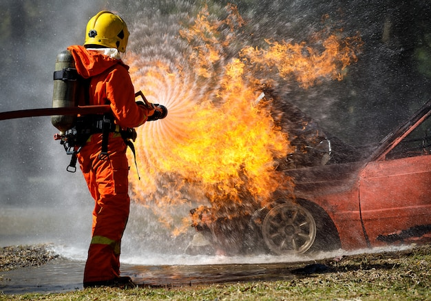 Vigile del fuoco che hosing l'acqua per estinguere un fuoco sopra l'automobile nell'incidente