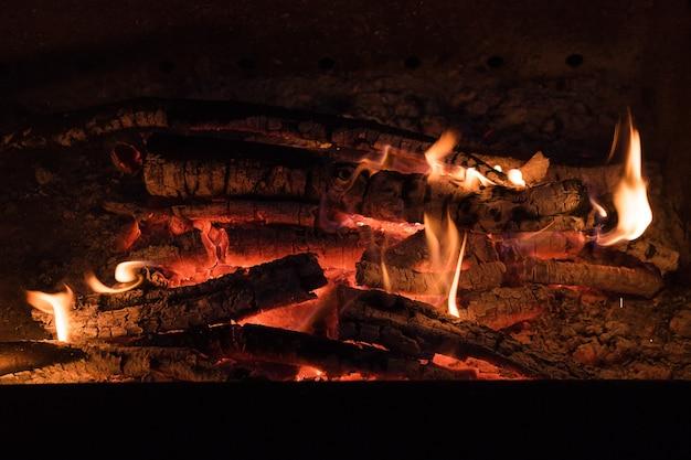 Fuoco in un caminetto da tronchi di legno conflagranti, ceppi in fiamme in un piccolo falò.