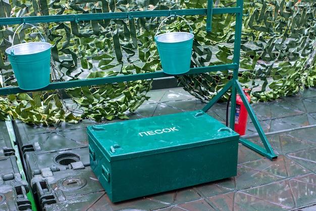 Sicurezza antincendio uno scudo antincendio un contenitore di metallo con il testo sabbia un secchio e un estintore per ...