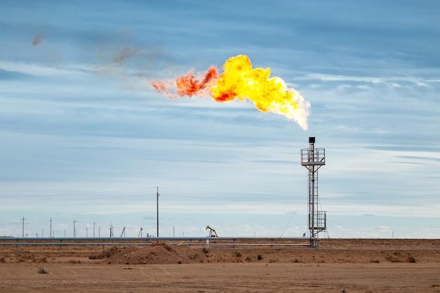 Spara su una pila di torce alla piattaforma di elaborazione centrale di petrolio e gas con il cielo blu sullo sfondo