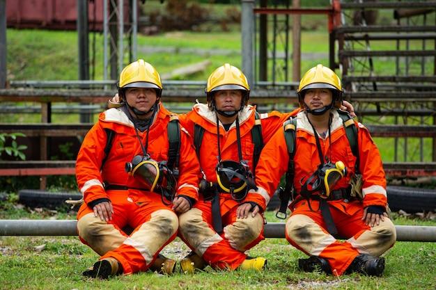 Squadra dei vigili del fuoco che si siede con la tuta di sicurezza dell'occupazione non stabile. professionista della lotta antincendio.