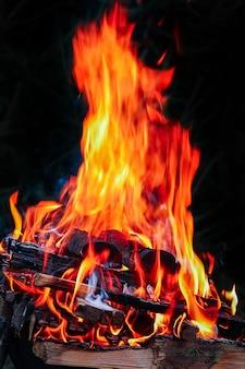 Un fuoco con carboni e fuoco sullo sfondo di picnic della natura. brucia un falò per il cibo per strada Foto Premium