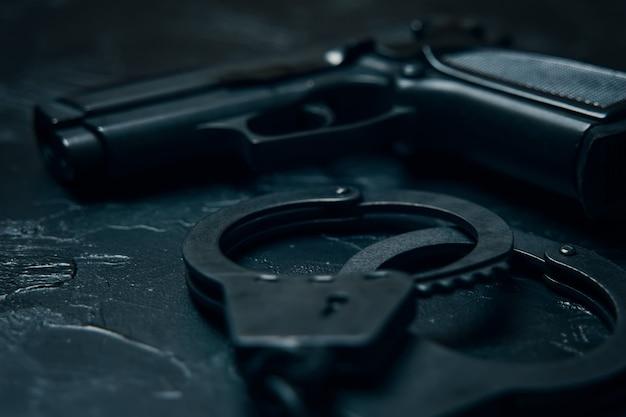Armi da fuoco e manette da vicino sulla pistola da tavola nera per le munizioni delle forze dell'ordine per l'arresto di criminali