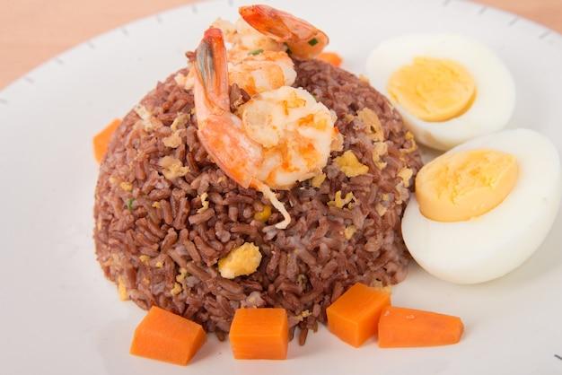 Riso integrale cotto con gamberetti, carote e uova sode cibo sano e pulito senza aggiunta di olio a basso contenuto di grassi