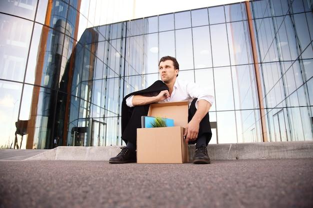 Uomo d'affari licenziato seduto frustrato e sconvolto per strada vicino all'edificio per uffici con una scatola delle sue cose. ha perso il lavoro