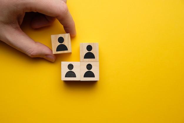 Concetto infornato - la mano tiene il blocco di legno con il lavoratore astratto su uno spazio giallo.
