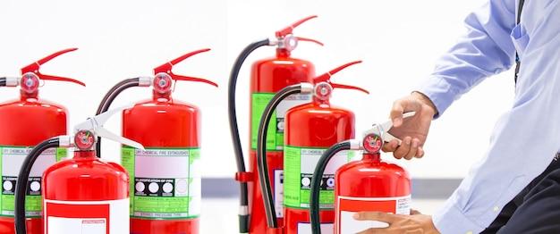 Pompiere che controlla la maniglia dell'estintore rosso