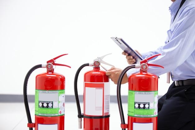 Vigile del fuoco che controlla il livello del manometro dell'estintore.