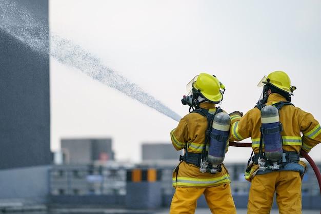 Vigile del fuoco o squadra di vigili del fuoco lavorano acqua nebulizzata dall'ugello ad alta pressione per sparare