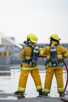 Vigile del fuoco o squadra di vigili del fuoco lavorano acqua nebulizzata dall'ugello ad alta pressione per sparare.