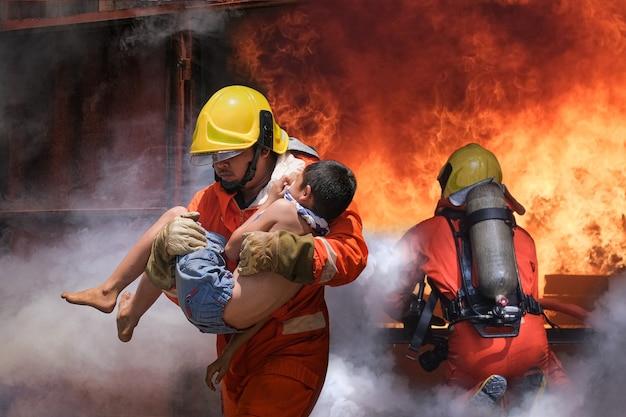 Vigile del fuoco che tiene bambino ragazzo per salvarlo in fuoco e fumo.