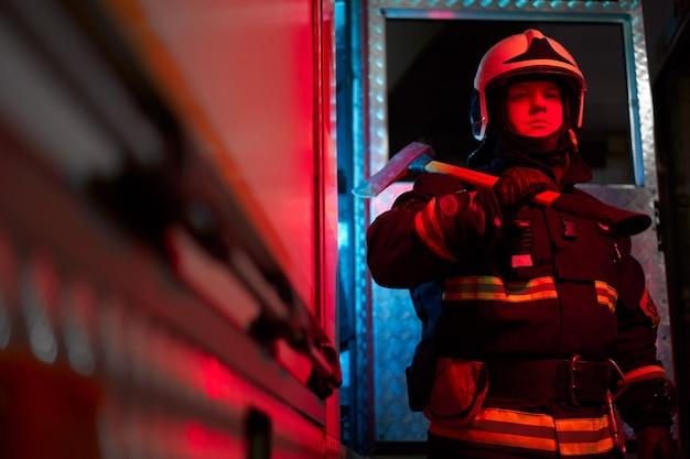 Vigile del fuoco maschio con martello sulla spalla in piedi vicino all'autopompa dei pompieri
