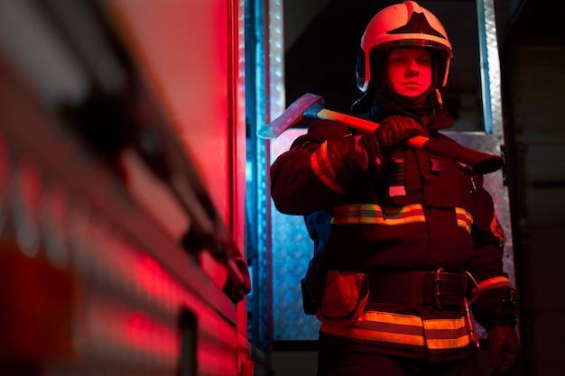 Vigile del fuoco con martello sulla spalla in piedi vicino all'autopompa