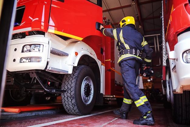 Vigile del fuoco che apre la porta del camion dei pompieri ed entra nella stazione dei vigili del fuoco. è preparato per l'azione.