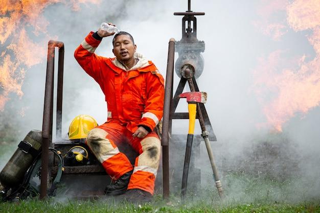 Vigile del fuoco che usa bere acqua per versare sulla testa dopo aver completato la missione. sedersi e rilassarsi accanto a un incidente di fuocoã â¹âƒ