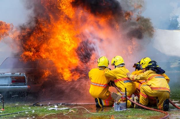 Pompiere che utilizza estintore e acqua dal tubo per antincendio