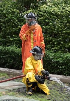 Vigile del fuoco in lotta antincendio ed evacuazione esercitazione di simulazione di trapano a percussione per sicurezza