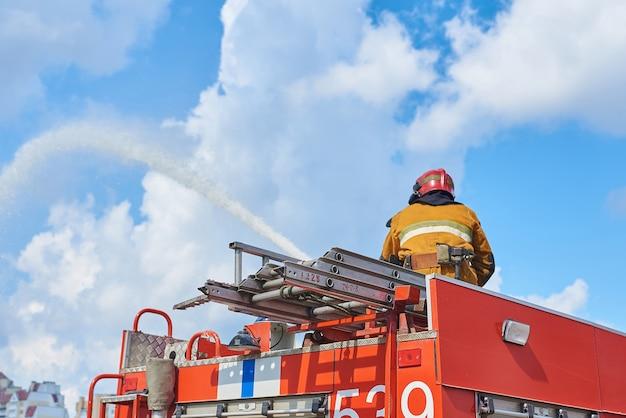 Vigile del fuoco sul tetto di un camion dei pompieri che innaffia da una manichetta antincendio