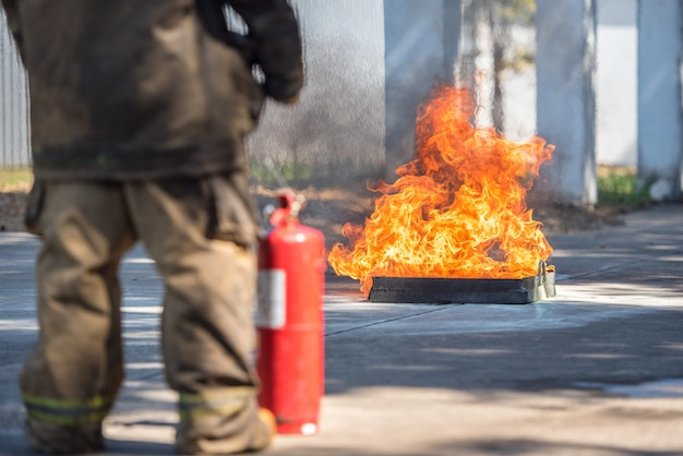 La rappresentazione del vigile del fuoco usa un estintore su un idrante di addestramento con fumo bianco. concetto di salute e sicurezza sul lavoro. Foto Premium