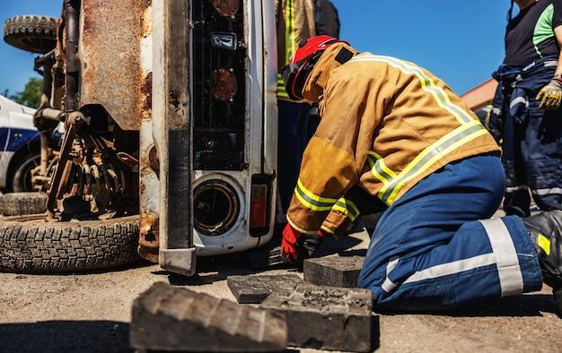 Vigile del fuoco che cerca di liberare l'uomo impilato in un'auto in un incidente d'auto.