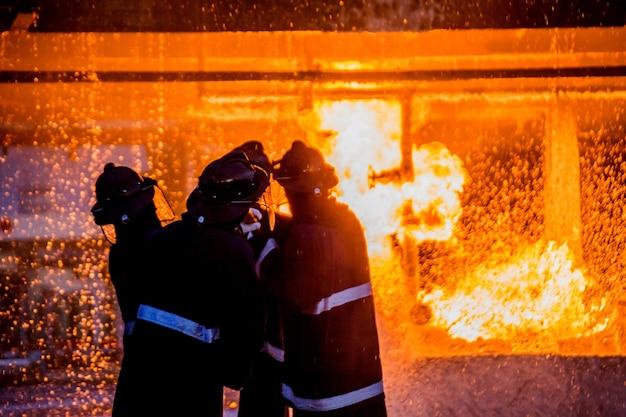 Vigili del fuoco che utilizzano l'acqua dal tubo per la lotta antincendio alla formazione degli scontri a fuoco del gruppo assicurativo