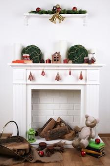 Camino con decorazioni natalizie su pavimento in legno vicino a sfondo bianco