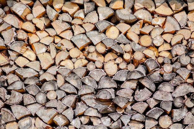 Sfondo di legna da ardere, parete di legna da ardere, sfondo di legna da ardere tritata secca registra in un mucchio.