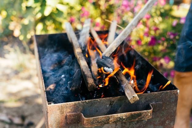 La legna da ardere brucia in un barbecue sullo sfondo della natura