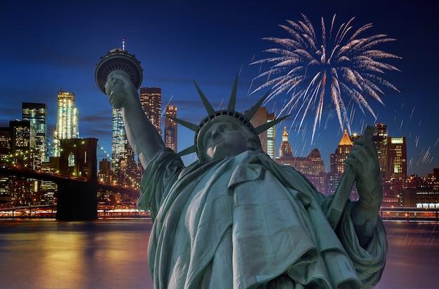 Fuochi d'artificio sulla città di new york di manhattan di notte con la statua della libertà a manhattan new york city usa celebrando il giorno dell'indipendenza degli stati uniti