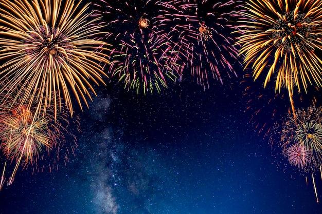 Fuochi d'artificio con sfocatura dello sfondo della via lattea