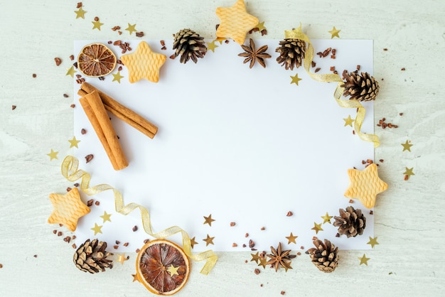 Abeti, biscotti, cannella e nastri dorati su fondo bianco. frame reeting scheda di capodanno. concetto di vacanze di natale. copia spazio, disteso