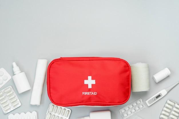 Borsa rossa del pronto soccorso con attrezzatura medica e medicine per il trattamento di emergenza. vista dall'alto piatto giaceva su sfondo grigio. copia spazio.