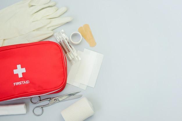 Borsa rossa di pronto soccorso con attrezzatura medica e farmaci per il trattamento di traumi e lesioni. vista dall'alto piatto giaceva su sfondo grigio. copia spazio.