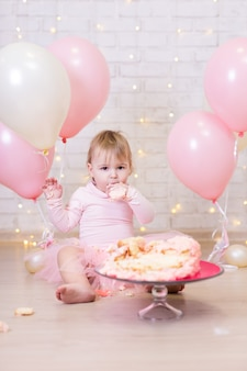 Prima festa di compleanno bambina divertente che mangia e rompe la torta sullo sfondo del muro di mattoni